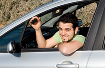 Young man sitting inside a car showing his keys