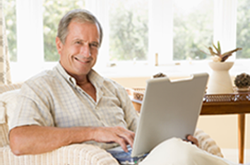 Mature man sitting on a couch smiling while holding a laptop.